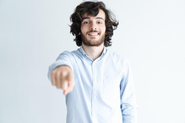 Uśmiechnięty młody człowiek wskazuje przy widzem i patrzeje kamerę