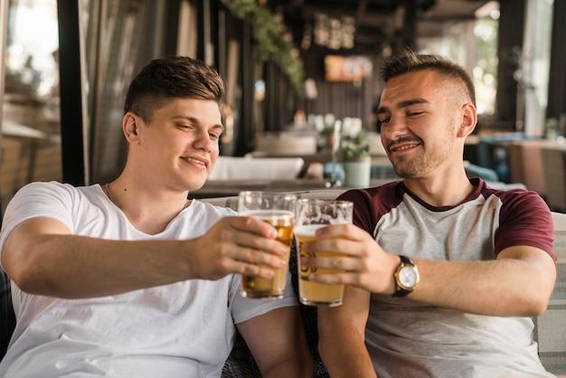 Uśmiechnięty młody człowiek wznosi toast piwni szkła w restauraci