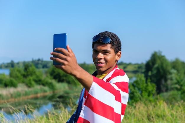 Uśmiechnięty młody człowiek z afryki, pokryty amerykańską flagą, biorący selfie