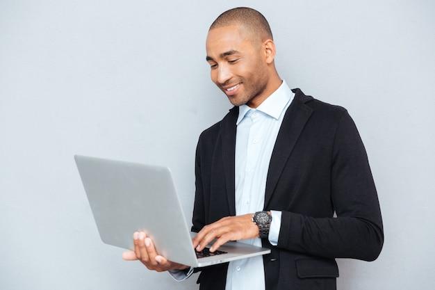 Uśmiechnięty młody człowiek z afryki, stojący i korzystający z laptopa