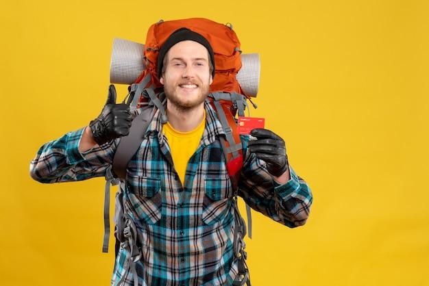 Uśmiechnięty młody człowiek z backpackerem trzymającym kartę rabatową dającą kciuk w górę