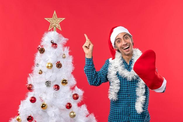 Uśmiechnięty młody człowiek z czapką świętego mikołaja w niebieskiej koszuli w paski i noszący swoją świąteczną skarpetę