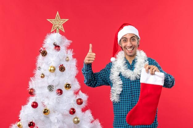 Uśmiechnięty młody człowiek z czapką świętego mikołaja w niebieskiej koszuli w paski i trzymając skarpetę świąteczną robi ok gest