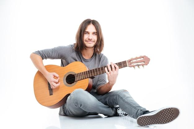 Uśmiechnięty młody człowiek z długimi włosami siedzi na podłodze i gra na gitarze na białym tle