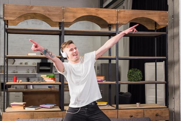 Uśmiechnięty młody człowiek z hełmofonem na jego głowie tanczy przed gablotą wystawową