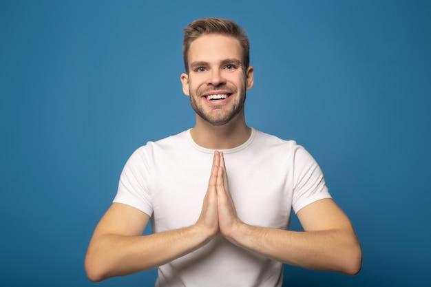 Uśmiechnięty młody człowiek z modlenie rękami odizolowywać na błękicie