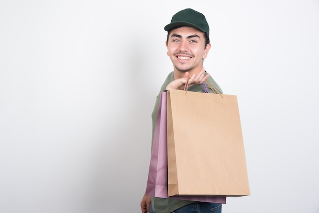 Uśmiechnięty młody człowiek z torby na zakupy na białym tle.