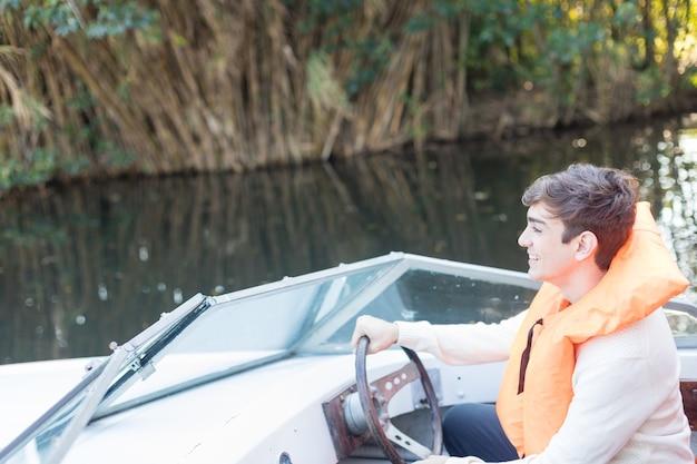 Uśmiechnięty młody człowiek za kierownicą łodzi