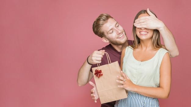 Uśmiechnięty młody człowiek zakrywa jej dziewczyn oczy trzyma torba na zakupy