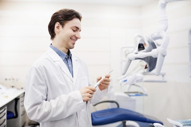 Uśmiechnięty młody dentysta