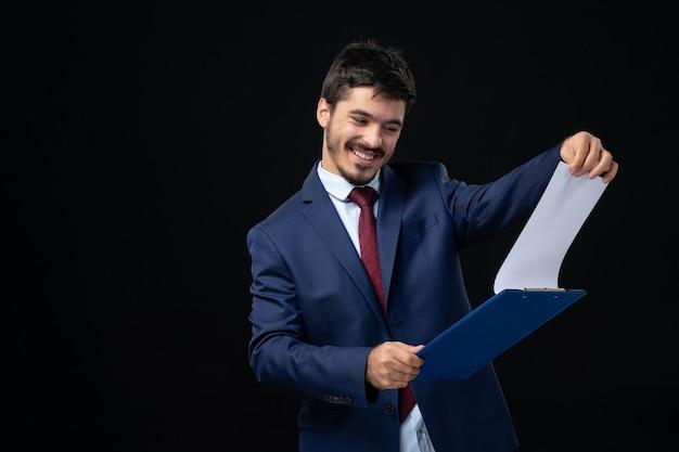 Uśmiechnięty młody dorosły w garniturze trzymający dokumenty i sprawdzający w nim statystyki na odizolowanej ciemnej ścianie