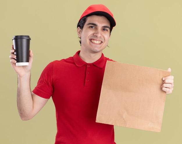 Uśmiechnięty młody dostawca w czerwonym mundurze i czapce, trzymający papierową paczkę i plastikową filiżankę kawy, patrzący na przód odizolowany na oliwkowozielonej ścianie