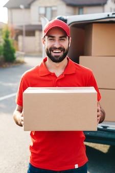 Uśmiechnięty młody dostawca w czerwonym mundurze stojący z pudełkiem na paczki w pobliżu samochodu na zewnątrz