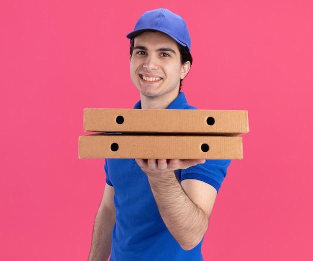 Uśmiechnięty młody dostawca w niebieskim mundurze i czapce stojący w widoku z profilu, trzymający paczki pizzy, patrzący na przód odizolowany na różowej ścianie