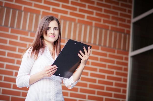 Uśmiechnięty młody elegancki bizneswoman z schowek pozycją w jaskrawym biurze