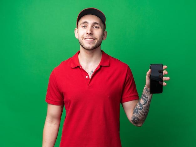 Uśmiechnięty młody facet dostawy ubrany w mundur z czapką trzymającą telefon