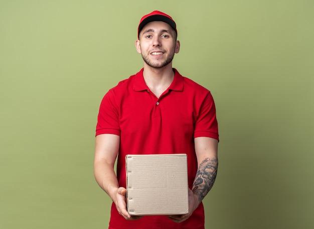 Uśmiechnięty młody facet od dostawy ubrany w mundur z czapką trzymającą pudełko