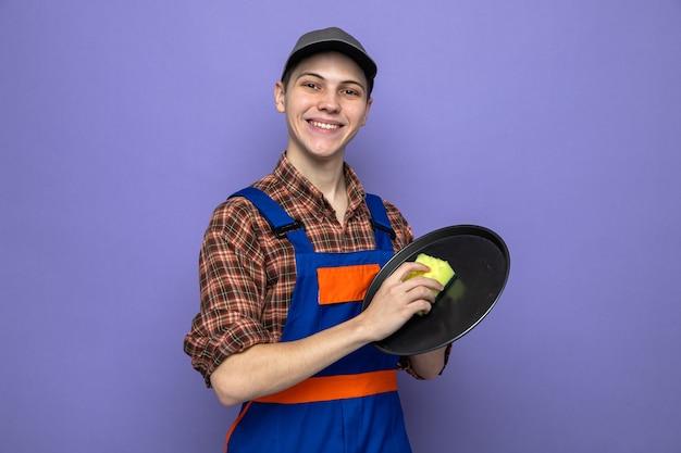 Uśmiechnięty młody facet sprzątający ubrany w mundur i tacę do mycia czapek z gąbką