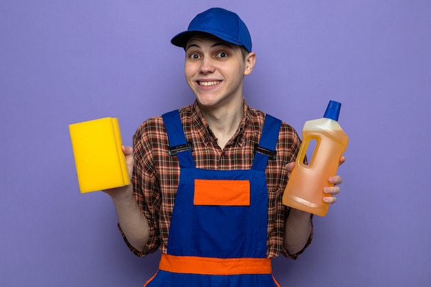 Uśmiechnięty młody facet sprzątający w mundurze i czapce trzymający środek czyszczący z gąbką