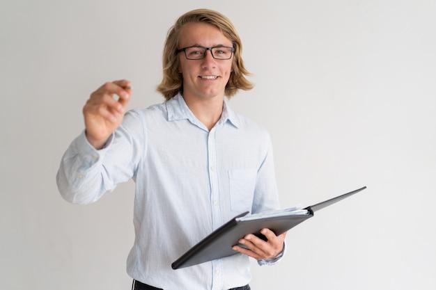 Uśmiechnięty młody facet trzyma falcówkę i pisze w powietrzu