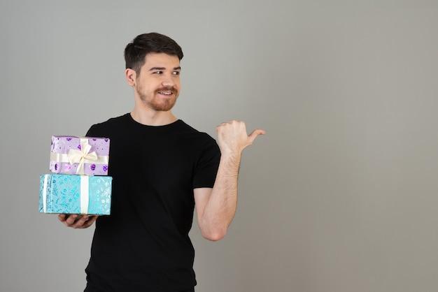 Uśmiechnięty młody facet trzyma prezent i pokazuje kciuk z boku.