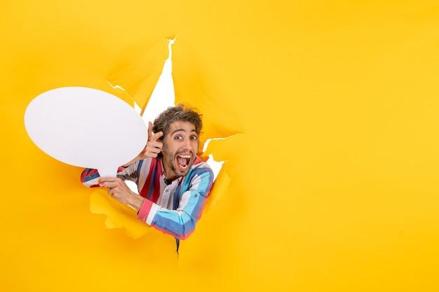 Uśmiechnięty młody facet trzymający biały balon i pozujący do kamery w rozdartej dziurze i wolnym tle w żółtym papierze