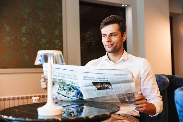 Uśmiechnięty młody formalnie ubrany mężczyzna czyta gazetę