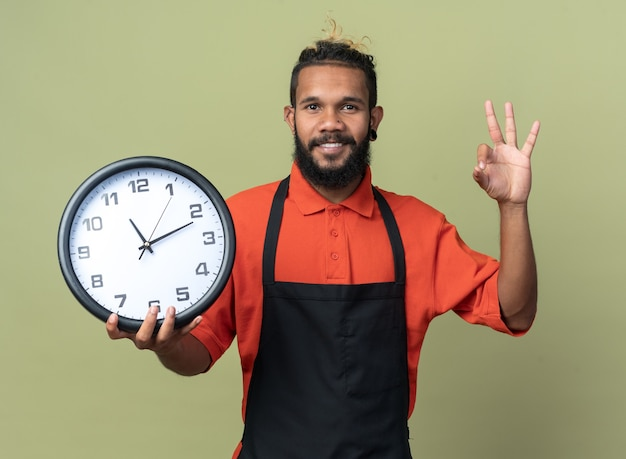 Uśmiechnięty młody fryzjer afroamerykański ubrany w mundur trzymający zegar, patrzący na kamerę, robiący ok znak na oliwkowozielonym tle