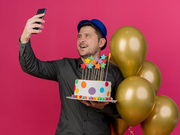 Uśmiechnięty młody imprezowicz w niebieskim kapeluszu stojący w pobliżu balonów trzymających tort i weź selfie na różowym tle