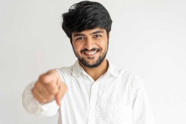 Uśmiechnięty młody indiański mężczyzna wskazuje przy tobą i patrzeje kamerę