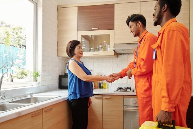 Uśmiechnięty młody indyjski hydraulik ściska rękę azjatyckiego właściciela domu po naprawie rury w kuchni