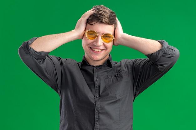 Uśmiechnięty młody kaukaski chłopak w okularach przeciwsłonecznych, kładący ręce na głowie i patrzący na kamerę