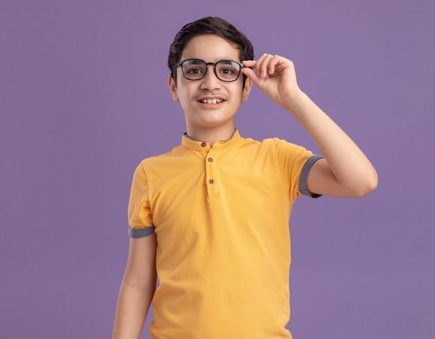 Uśmiechnięty młody kaukaski chłopiec noszący i chwytający okulary izolowane na fioletowej ścianie z miejscem na kopię