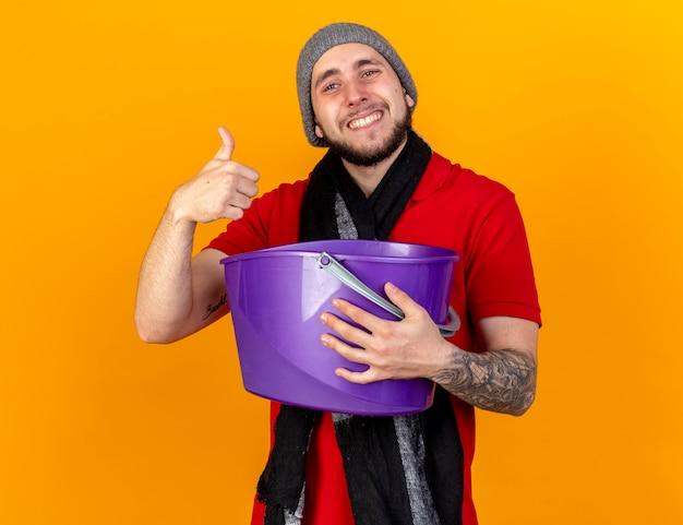 Uśmiechnięty młody kaukaski chory czapka zimowa i szalik trzyma plastikowe wiadro i kciuki do góry na białym tle na pomarańczowej ścianie z miejsca na kopię