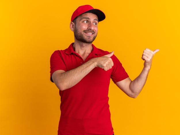 Uśmiechnięty młody kaukaski dostawca w czerwonym mundurze i czapce, patrzący na bok pokazując kciuk do góry odizolowany na pomarańczowej ścianie