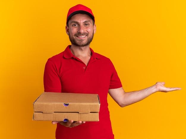 Uśmiechnięty młody kaukaski dostawca w czerwonym mundurze i czapce, patrzący na kamerę trzymającą paczki pizzy pokazujące pustą rękę odizolowaną na pomarańczowej ścianie