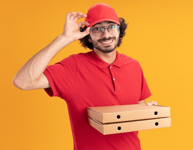 Uśmiechnięty młody kaukaski dostawca w czerwonym mundurze i czapce w okularach chwytający czapkę trzymającą paczki pizzy na pomarańczowej ścianie