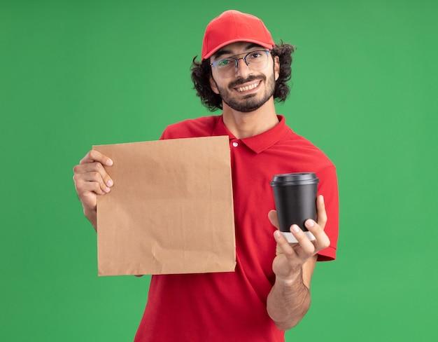 Uśmiechnięty młody kaukaski dostawca w czerwonym mundurze i czapce w okularach trzymających papierową paczkę i plastikową filiżankę kawy na zielonej ścianie