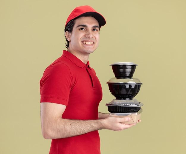 Uśmiechnięty młody kaukaski dostawca w czerwonym mundurze i czapce
