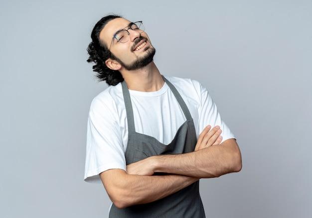 Uśmiechnięty młody kaukaski fryzjer męski w okularach i falistej opasce do włosów w mundurze stojącym z zamkniętą posturą z zamkniętymi oczami na białym tle z miejscem na kopię