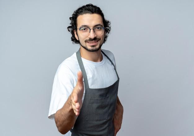 Uśmiechnięty młody kaukaski fryzjer męski w okularach i falistej opasce do włosów w mundurze wyciągając rękę w kierunku aparatu, gestykulując cześć na białym tle z miejsca na kopię