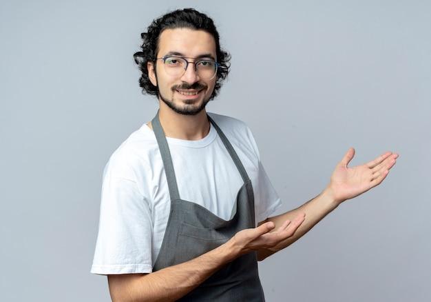 Uśmiechnięty młody kaukaski fryzjer męski w okularach i falującą opaską do włosów w mundurze, wskazując na bok rękami na białym tle