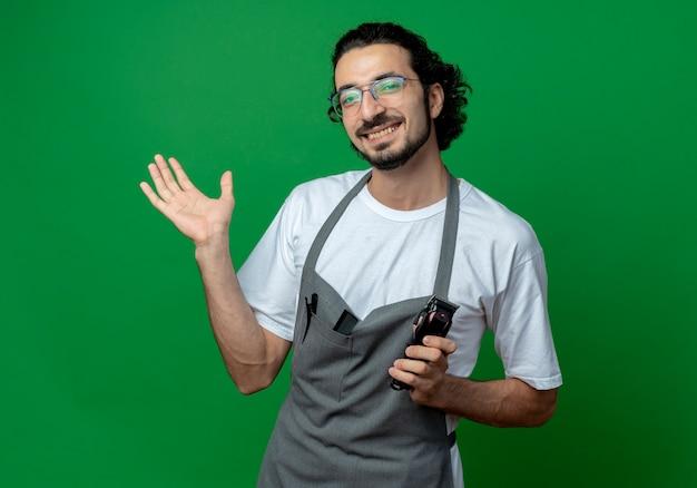 Uśmiechnięty młody kaukaski fryzjer męski w okularach i falującej opasce do włosów w mundurze trzyma maszynkę do strzyżenia włosów i pokazuje pustą dłoń odizolowaną na zielonym tle z miejscem na kopię
