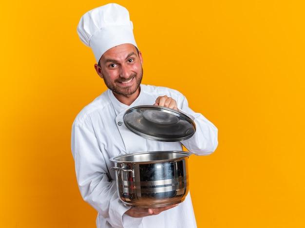 Uśmiechnięty młody kaukaski kucharz w mundurze szefa kuchni i czapce otwierającej pokrywkę garnka