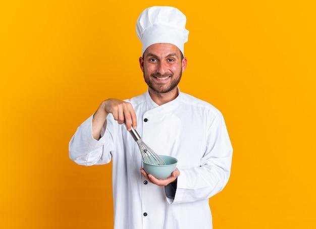 Uśmiechnięty młody kaukaski kucharz w mundurze szefa kuchni i czapce, patrząc na kamerę ubijającą jajka z trzepaczką w misce na pomarańczowej ścianie