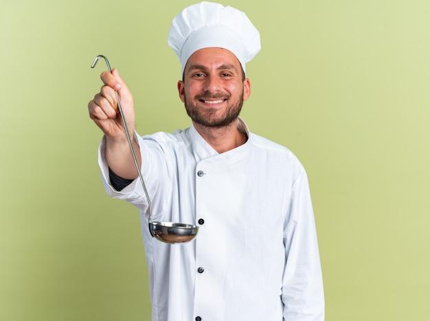 Uśmiechnięty młody kaukaski kucharz w mundurze szefa kuchni i czapce, patrząc na kamerę wyciągającą kadzi w kierunku kamery izolowanej na oliwkowozielonej ścianie