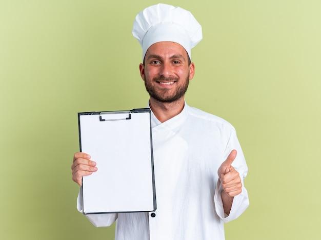 Uśmiechnięty młody kaukaski kucharz w mundurze szefa kuchni i czapce, patrzący na kamerę pokazującą schowek i kciuk na białym tle na oliwkowozielonej ścianie