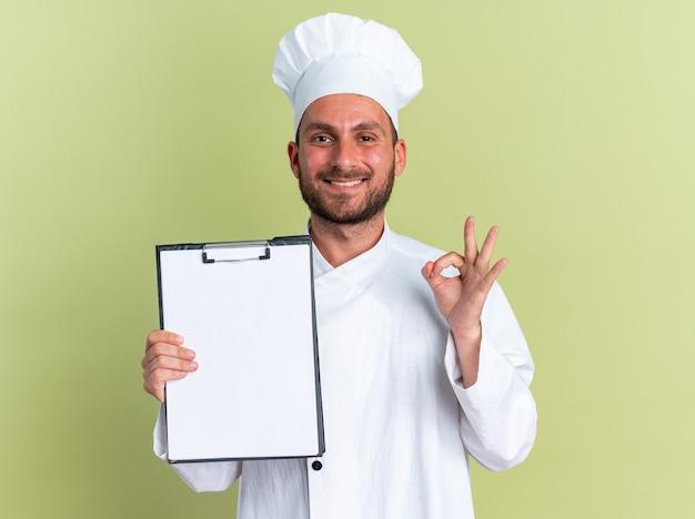 Uśmiechnięty młody kaukaski kucharz w mundurze szefa kuchni i czapce, patrzący na kamerę pokazującą schowek robiący znak ok na oliwkowozielonej ścianie