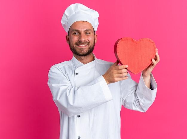 Uśmiechnięty młody kaukaski kucharz w mundurze szefa kuchni i czapce pokazującej kształt serca heart