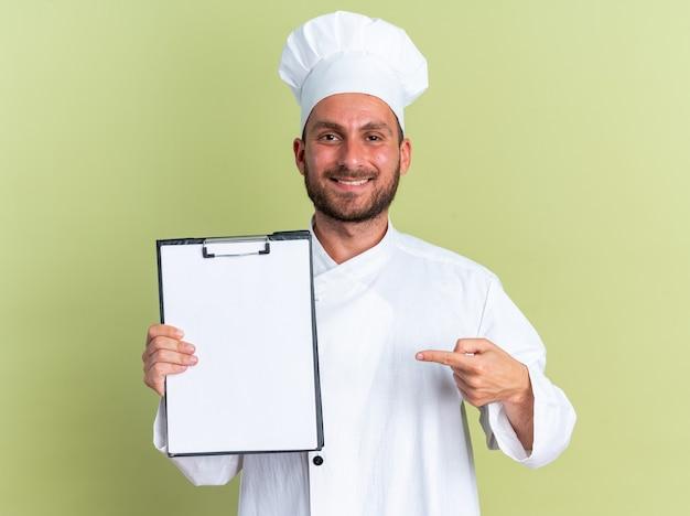 Uśmiechnięty młody kaukaski kucharz w mundurze szefa kuchni i czapce pokazujący i wskazujący na schowek